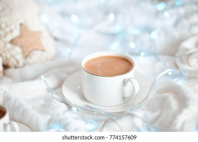 Cup of cappuccino or hot chocolate , cacao with christmas decoration like it  slippers and lights. White and blue colors. Bedroom background. Winter style