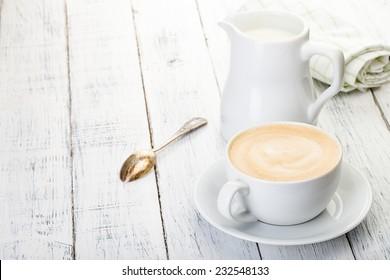 taza de cappuccino y jarra de leche sobre una mesa de madera blanca pintada.