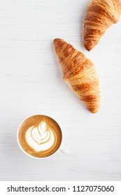 A cup of cappuccino with latte art and two croissants on white wooden table. Traditional french breakfast. Top view.