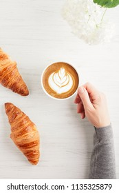 A cup of cappuccino with latte art and two croissants on white wooden table. Traditional french breakfast. Woman's hand holding a cup of coffee. Top view.