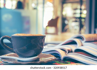 Cup of cappuccino with magazine on blur coffee shop background, vintage tone