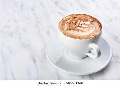Cup of cappuccino on the table, coffee shop background. Marble texture