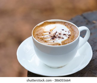 Cup of Cappuccino on wooden  table with chocolate