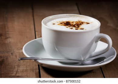 cup of cappuccino on wooden table