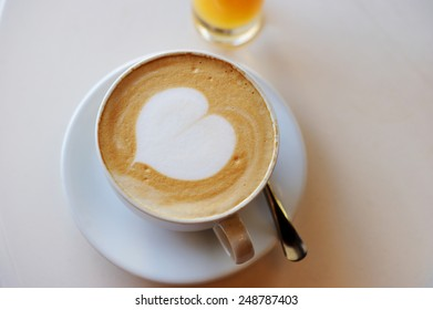 A cup of cappuccino over white  table with heart pattern