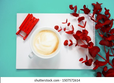 Cup of cappuccino with red eucalyptus on trendy neo mint color background .