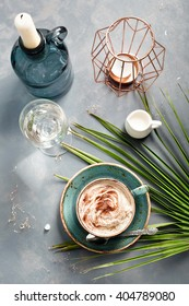 Cup of cappuccino set with modern and exotic accessories - palm leaf, candles and candle holders. Chilling out at bar by sea/ coffee consuming/holiday and travel concepts.