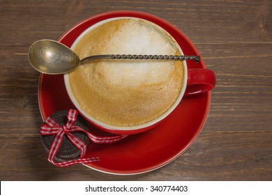 Cup of Cappuccino with spoon and cookie.
