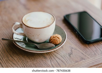 cup of cappuccino with a spoon and cookies on a saucer on the table with a cell phone. Wooden texture of the table.