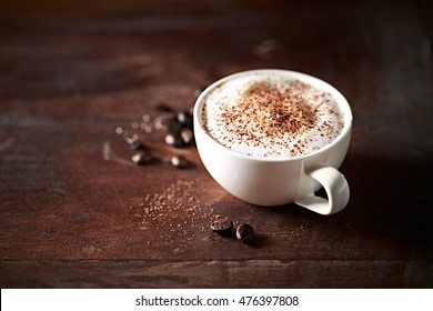 Cup of Cappuccino topped with Cocoa on dark wooden background. Copy space