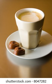 A cup of cappuccino with two coffee chocolates