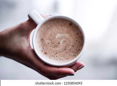 a cup of cappuccino in a woman's hand
