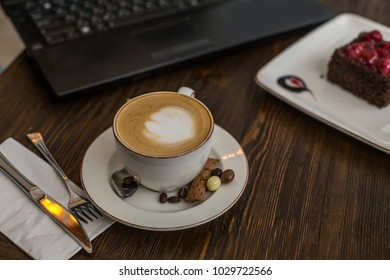 A cup of cappuchino on wooden tabletop with laptop keyboard and piece of chocolate cake blurred in the background