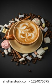 Cup of cappucino decorated with beans and marshmallow