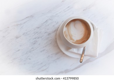 A cup of cappucino on a white table