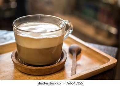 A cup of capuccino latte art coffee and spoon on wooden table background.