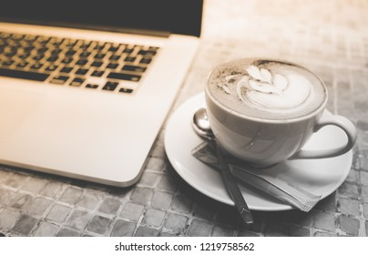 A cup of capuchino coffee or latte coffe in a white cup with laptop on table. Royalty high quality free stock photo of drink capuchino or latte coffe with laptop for working in office