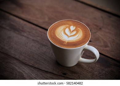 a cup of capuchino coffee on wooden table with copy space