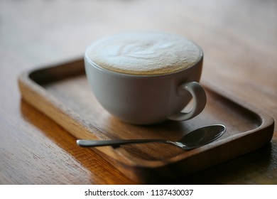 A cup of capuchino coffee with spoon on wooden table.