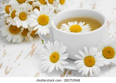 A cup of chamomile tea with a bouquet of daisies on a wooden background