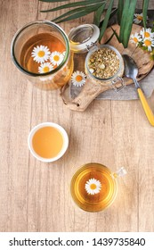 Cup of Chamomile Tea with chamomile flowers. Herbal Tea with fresh chamomile flowers on a wooden table.