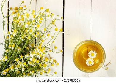 cup of chamomile tea with chamomile flowers on white wooden planks