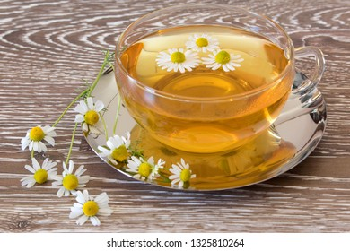 cup of chamomile tea with fresh blossoms