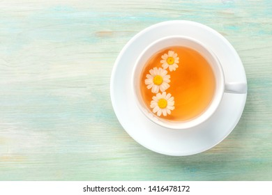 A cup of chamomile tea with steeping flowers, shot from the top on a teal blue background with a place for text