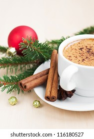 Cup of Christmas cappuccino on holiday background