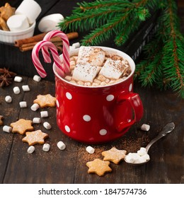 A cup of Christmas hot chocolate with candies and lollipops, next to it star cakes and Christmas decorations. Happy new 2021 to all who celebrate.