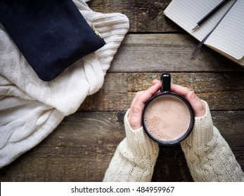Cup of cocoa in hands and office  staff on wooden table