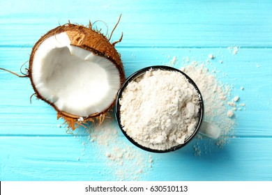 Cup with coconut flour and half of nut on wooden background