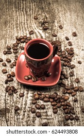 Cup of cofee and coffee beans on old gray wooden table. Selective focus. Shallow depth of field. Toned.