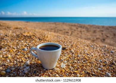 cup of cofee on a sandy sea beach