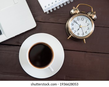 cup of coffe with clock and notebook on working table