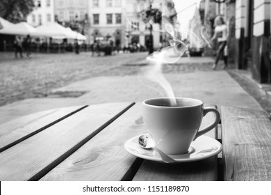 cup of coffe on the table of the outdoor cafe on the italian city sidewalk. Black and white photo