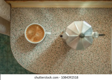 Cup of coffe and pot on marble table at the kitchen