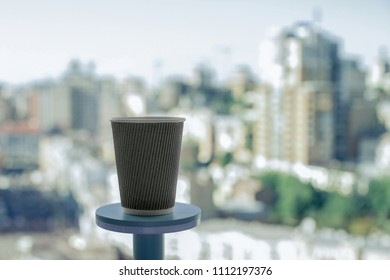 Cup of coffe standing on the urban jungle background.