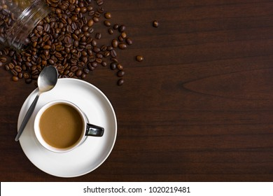 Cup of coffee from above, lay flat image, with coffee beans on wood table.