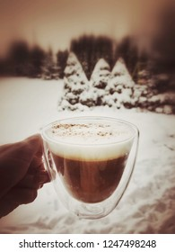 a cup of coffee against garden under snow