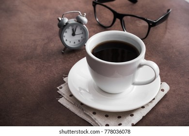Cup of coffee with alarm clock on table and black glasses, office break concept, vintage concrete background
