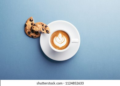 A cup of coffee and american cookies with chocolate chips on grey background. Top view.