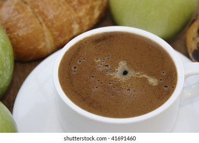 Cup of coffee, apples and croissant.