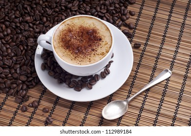 Cup of coffee arranged with  fresh roasted coffee beans on a wooden background