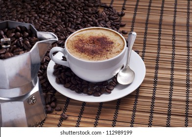 Cup of coffee arranged with  fresh roasted coffee beans and Italian coffee-maker on a wooden background