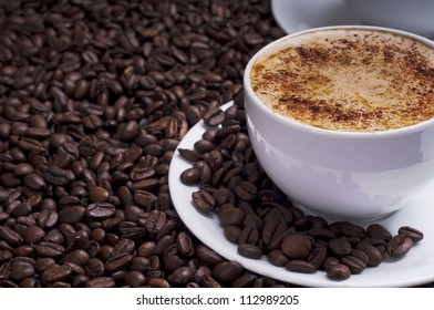 Cup of coffee arranged with  fresh roasted coffee beans