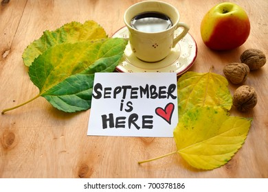Cup of coffee with autumn leaves and an apple and September is here text on a note on wooden table
