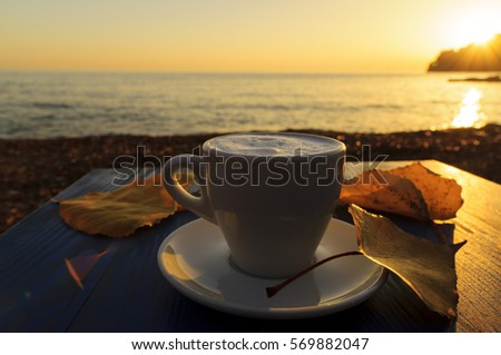 A cup of coffee in the autumn at sunset by the sea