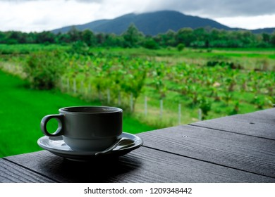 A cup of coffee. Background bokeh: farm and mountain
