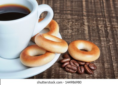 A cup of coffee with baked bagels, close-up. Coffee beans on the wooden background.